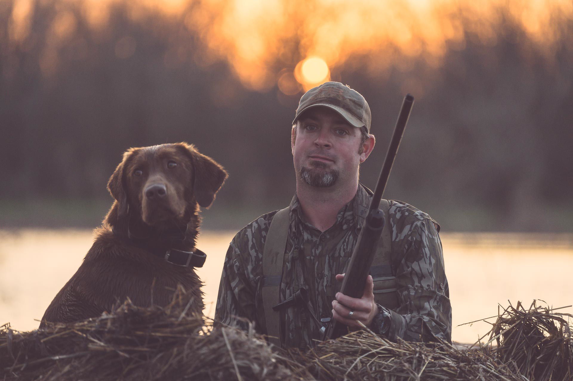 Richard, duck hunting guide and dog trainer with his prized chocolate lab in a floating duck blind at sunset, Honey Brake. © Tony Bynum