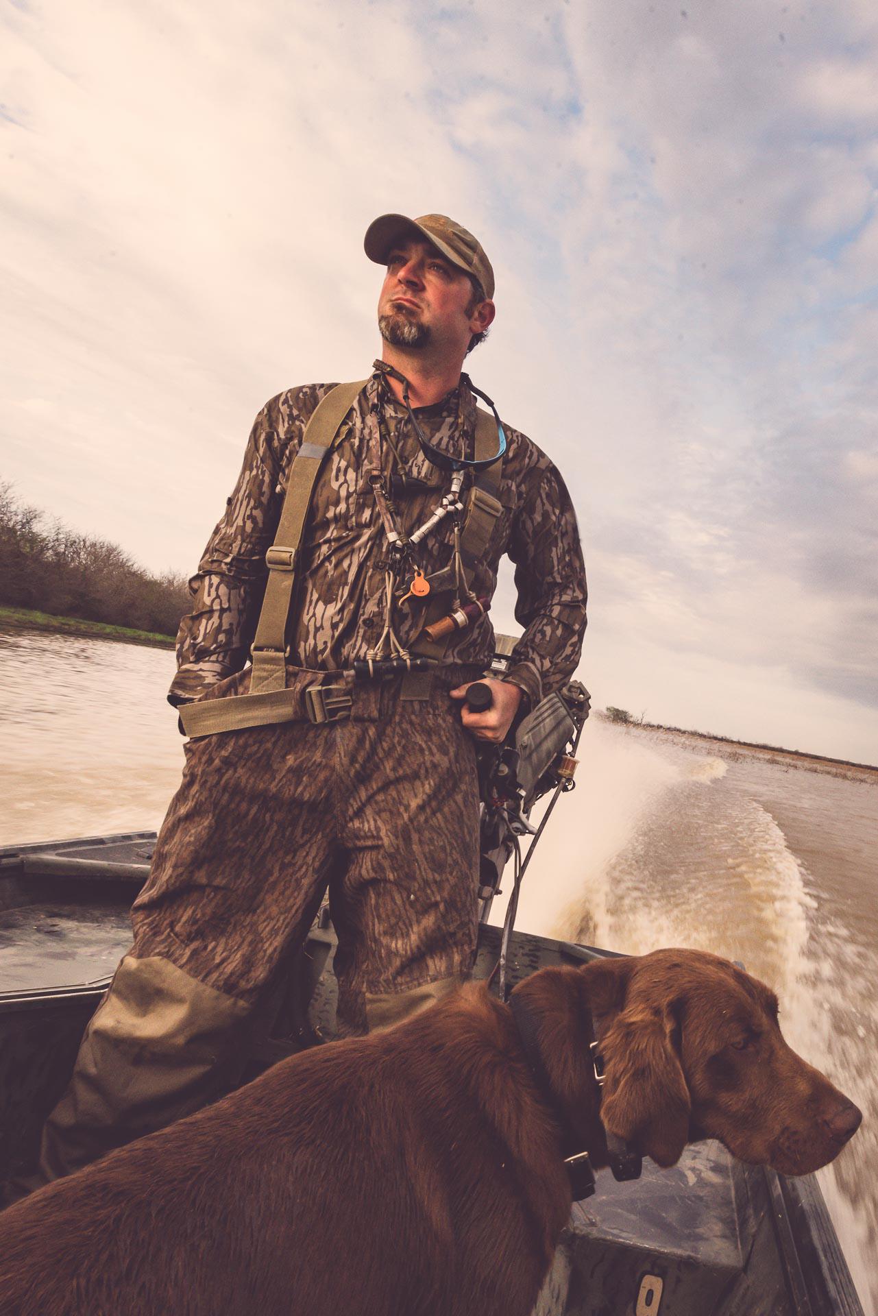 Richard and his dog speeding across the marsh in a boat at Honey Brake. © Tony Bynum