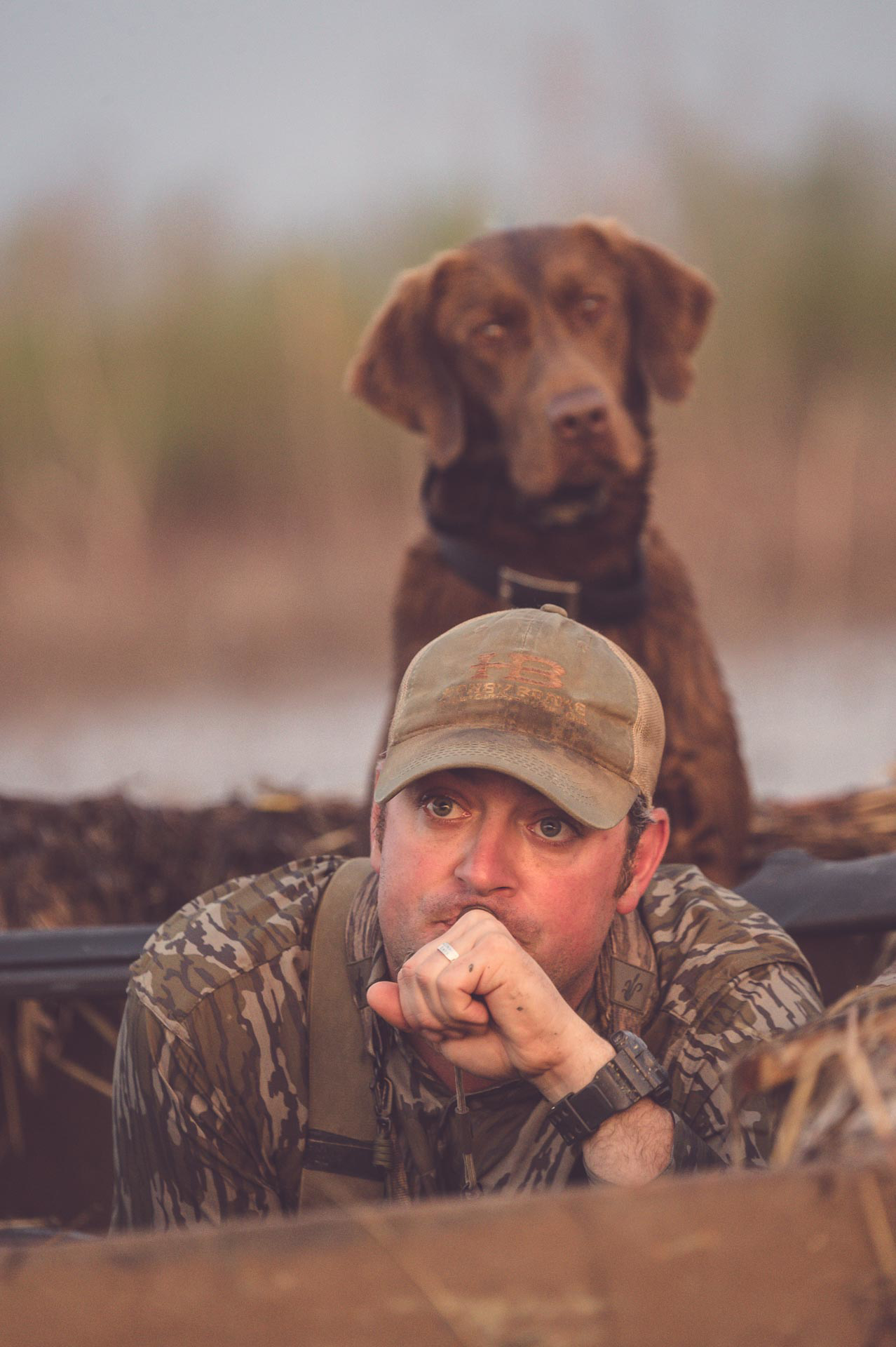 Duck hunting guide, Richard, calling ducks while his lab watches. © Tony Bynum