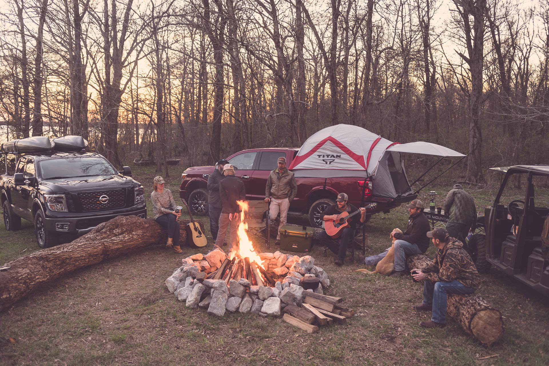 Group of hunters around a fire listening to music next to their Nissan Titan Trucks. © Tony Bynum