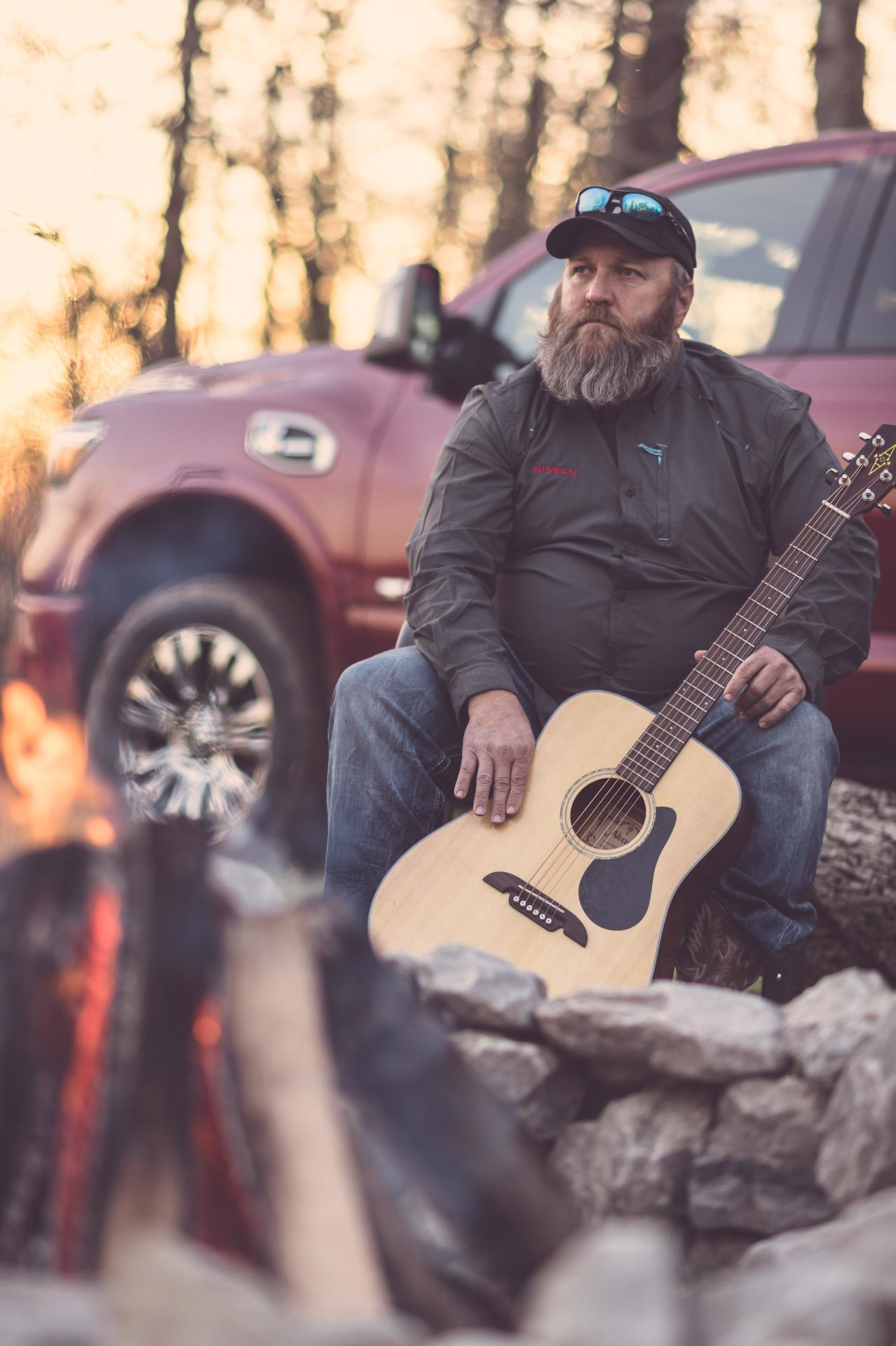 Sitting by fire waiting to play guitar. © Tony Bynum