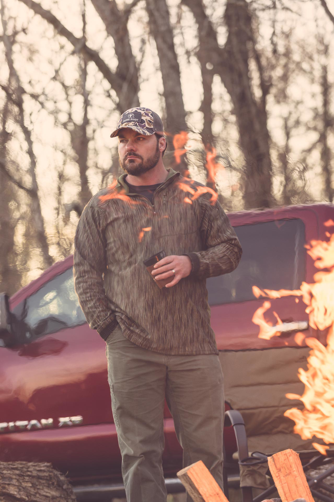 Duck hunter wearing a Voormi wool shirt standing near a fire in front of a Nissan Titan. © Tony Bynum