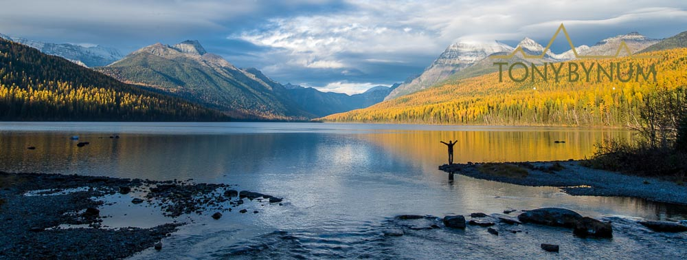 Fall in Glacier National Park - Stacy Dolderer stands on the edge of a lake in beautiful Glacier National Park. © Tony Bynum