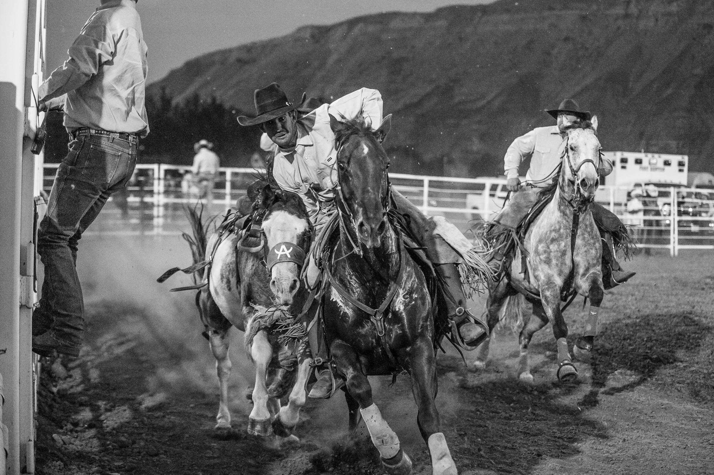 Pickup Men chasing down a bronc in the arena. © Tony Bynum