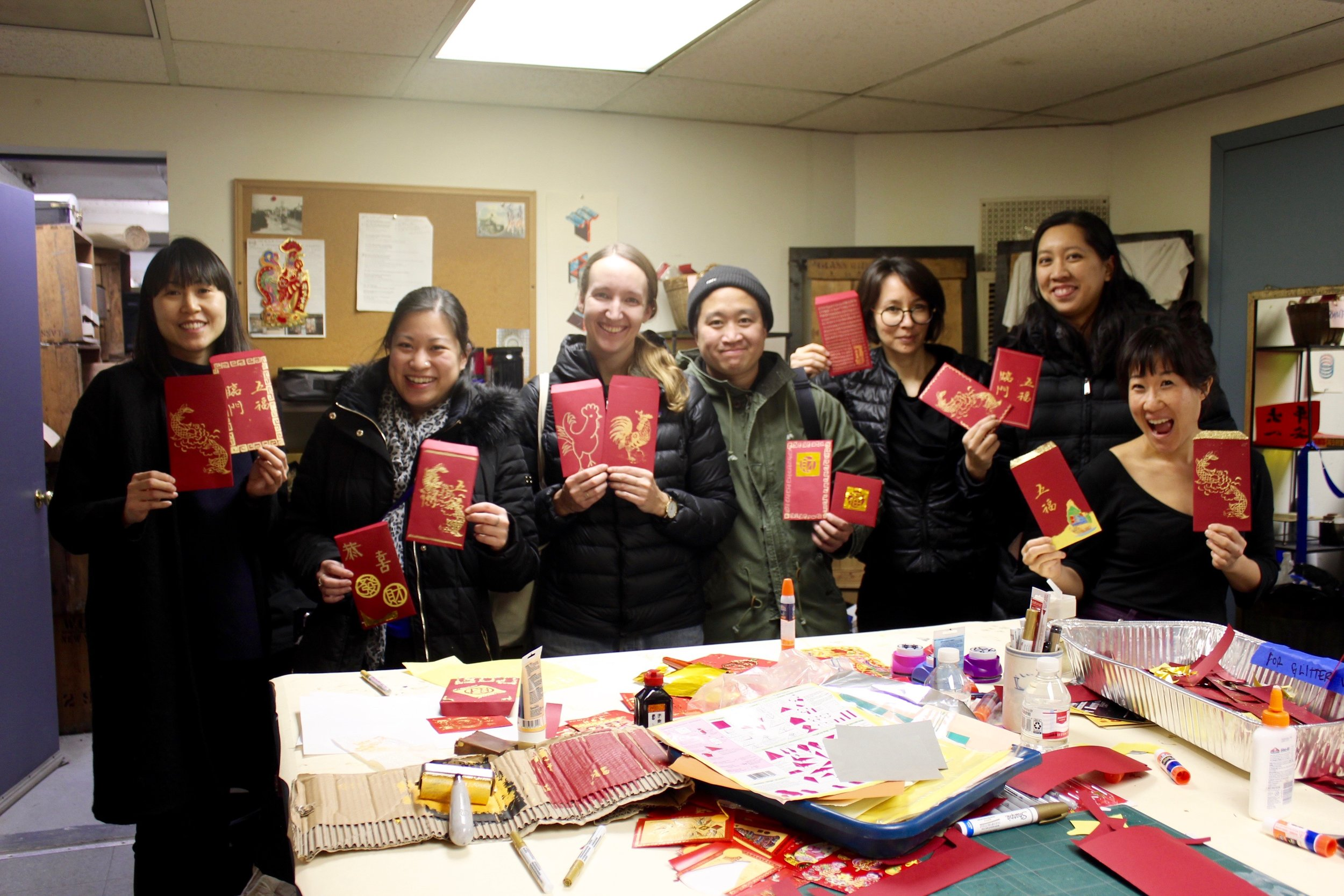 Workshop participants pose with their red envelopes in W.O.W's screen-printing studio.