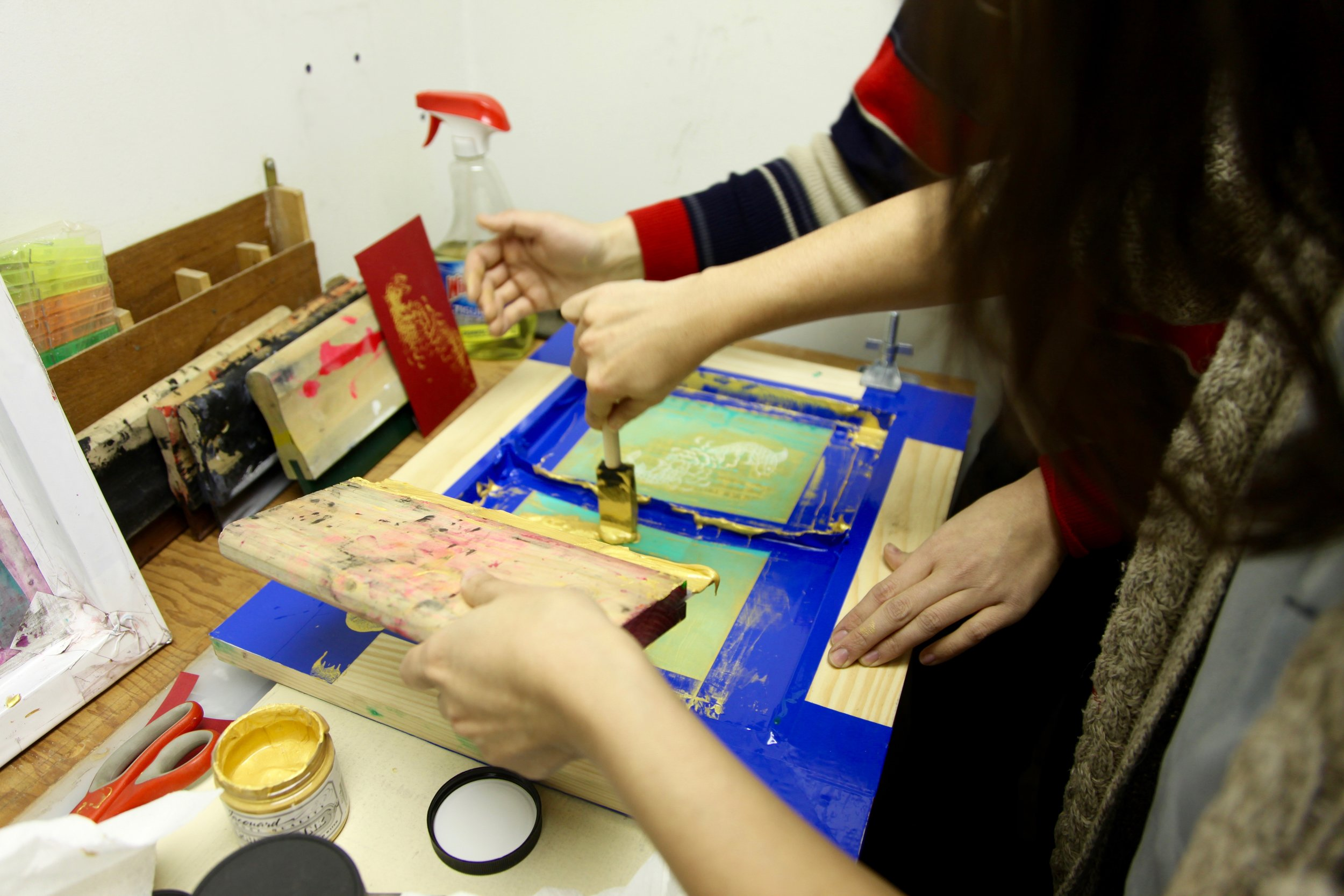 A participant silkscreens a rooster design onto her red envelope in W.O.W's screen-printing studio.