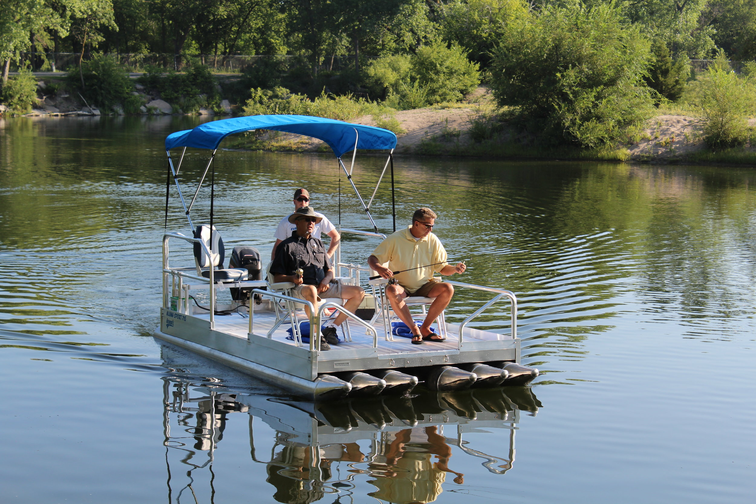 """Check out the 716 Aluma Sport pontoon boat we introduced for the first time in early 2018. With 1,600 lbs. of capacity and a 25 hp rating, you will have the ability to carry more weight and move across the lake at faster speeds to get to those favorite fishing holes or locations across the water. ( Boat above is shown with optional canopy top, seating and 25 hp. outboard motor.)    This 7' wide x 16' long all aluminum pontoon boat is packed with ( 6 ) 12"""" floats that by far give it the most stable platform in the industry for a boat this size. Pontoons are .090 thick aluminum, with .100 thickness on cones and end caps.( That is the heaviest in the industry ) The 716 Aluma Sport weighs 875 lbs, with the trailer weighing 620 lbs. for a combined pulling weight of 1,495 lbs. That makes it very easy to pull with the lightest pickup or like vehicle on the road.    We are personally involved with every boat we have ever designed or manufactured, and after 2 years in development, we can say, this boat is incredible when it comes to maneuverability and stability. We have just never seen anything like it on the water. This craft is literally like walking around on your patio.    Quality, you need not question the construction of this boat, like all our pontoon boats and docks we manufacture, there is nothing to compare them to. The 716 Aluma Sport is manufactured completely of aluminum with stainless steel hardware. We tell people everyday they could bury this boat, dig it up 20 years later and go boating.    NOTE:    We get asked regularly if that aluminum floor is going to get hot and be uncomfortable to walk on with bare feet. Aluminum is 11 degrees cooler than wood in the same sun light, as it reflects the heat instead of absorbing it. Also, after you have owned this craft a few months that floor will patina, taking that shine out of the aluminum making it absolutely as cool as anything out there to walk on."""