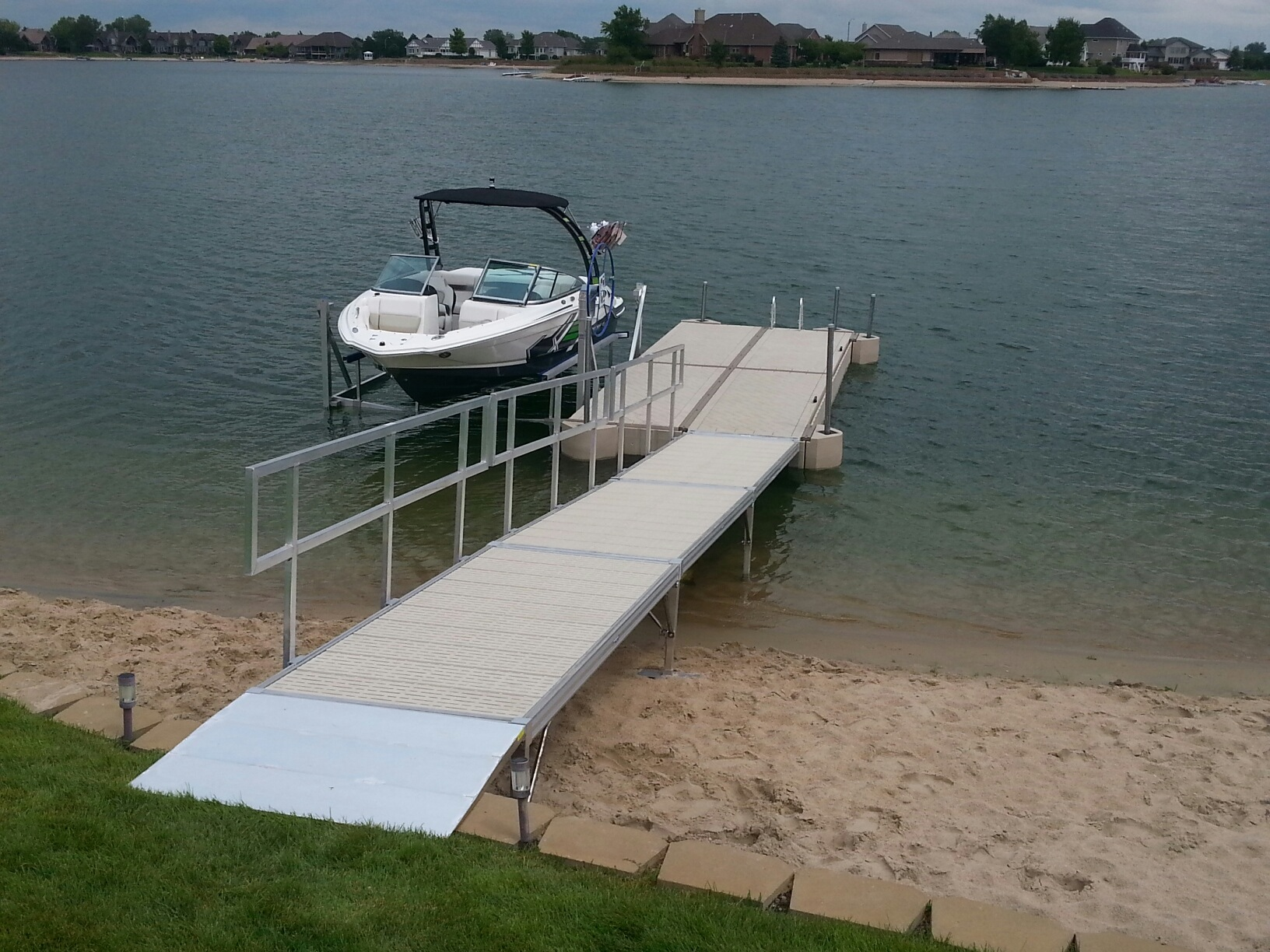Shoremaster poly dock with Shoremaster aluminum lift installed by Hotwoods in Grand Island, Ne. Complete with Hotwoods custom seawall bridge aluminum entry ramp.