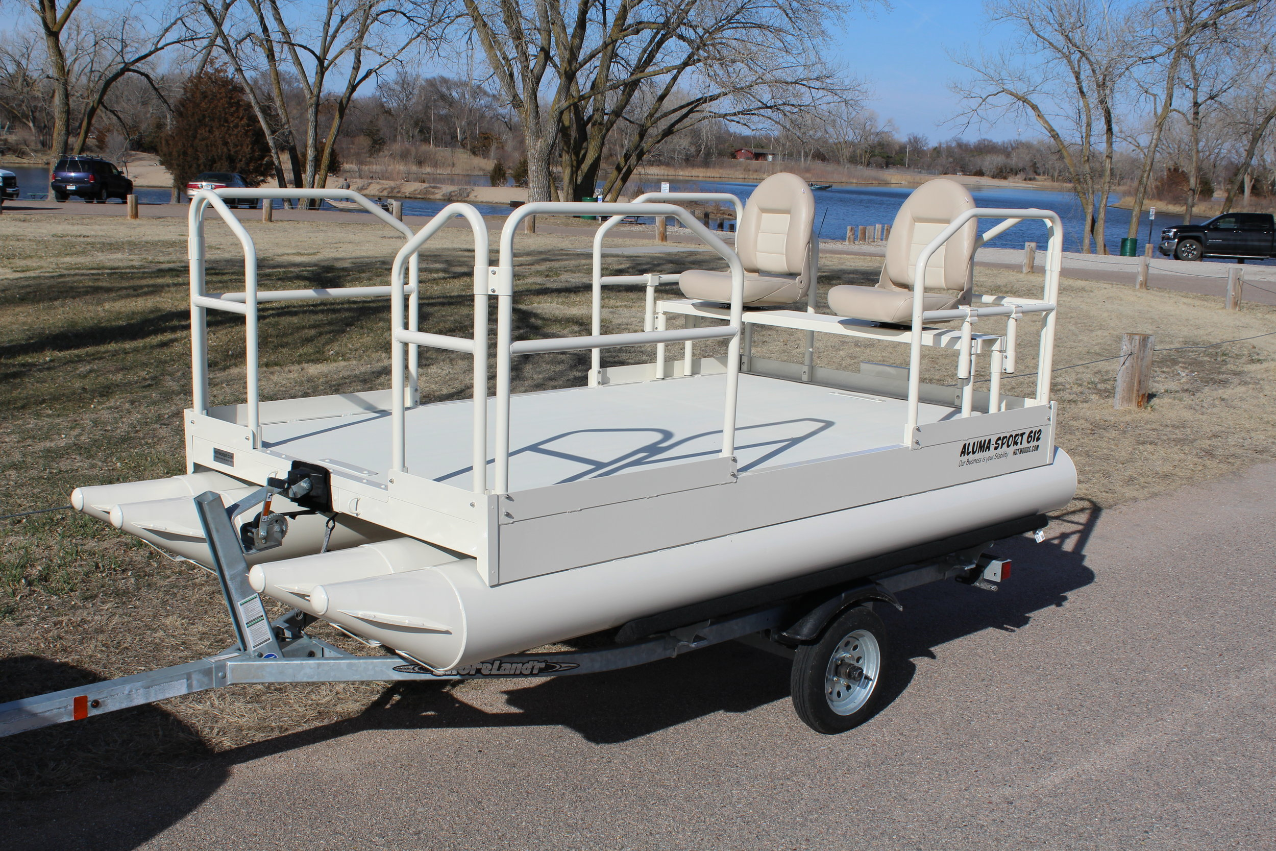 """612 Aluma Sport shown in custom color, Cedar Rapids White. This customer added the optional 34"""" handrails all around and the up graded folding seats.  Hotwoods offers premium powder coating to all out pontoon models except the 716 Aluma Sport. This color was a custom color that we normally do not offer, but was requested by this customer. Hotwoods filled the wish to give the customer exactly what they wanted. It is a very creamy white that is a real hit with everyone that has seen it so far.  Customers ask, what is the price difference of a custom color? The answer to that is, there is an up charge for premium powder coating and it can vary depending on color. Remember, we will always go that extra mile to give you what you want and at the same time, doing it the most economical way possible, for you the customer."""