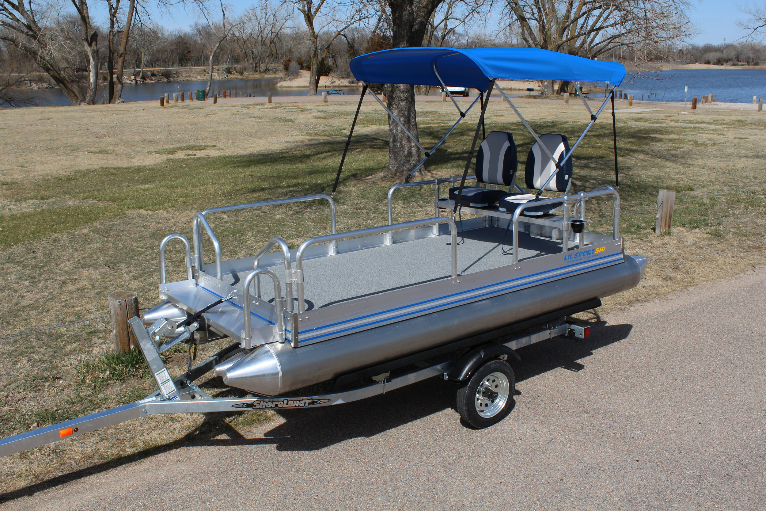 Lil Sport shown with optional canopy, bench seat, 2 swivel high back cushion seats bolted to that bench and the Shoreland'r galvanized trailer. This makes the perfect set up for those hard to get to lakes or the smaller ponds and lakes that we all know harbor some of the best fishing there is.
