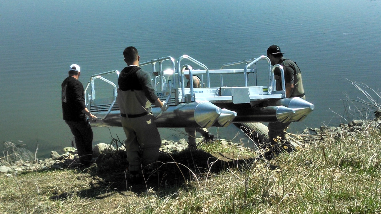 With the weight of the Fish N Sport at 405 pounds it is very easy for 4 men to carry it to hard to get to spots like this lake in Colorado that did not have a ramp to unload it from the trailer. Also the side rescue rails are a great aid to the men carrying the boat as you see in the photo. These rails can be added to any Hotwoods pontoon boat we manufacture.