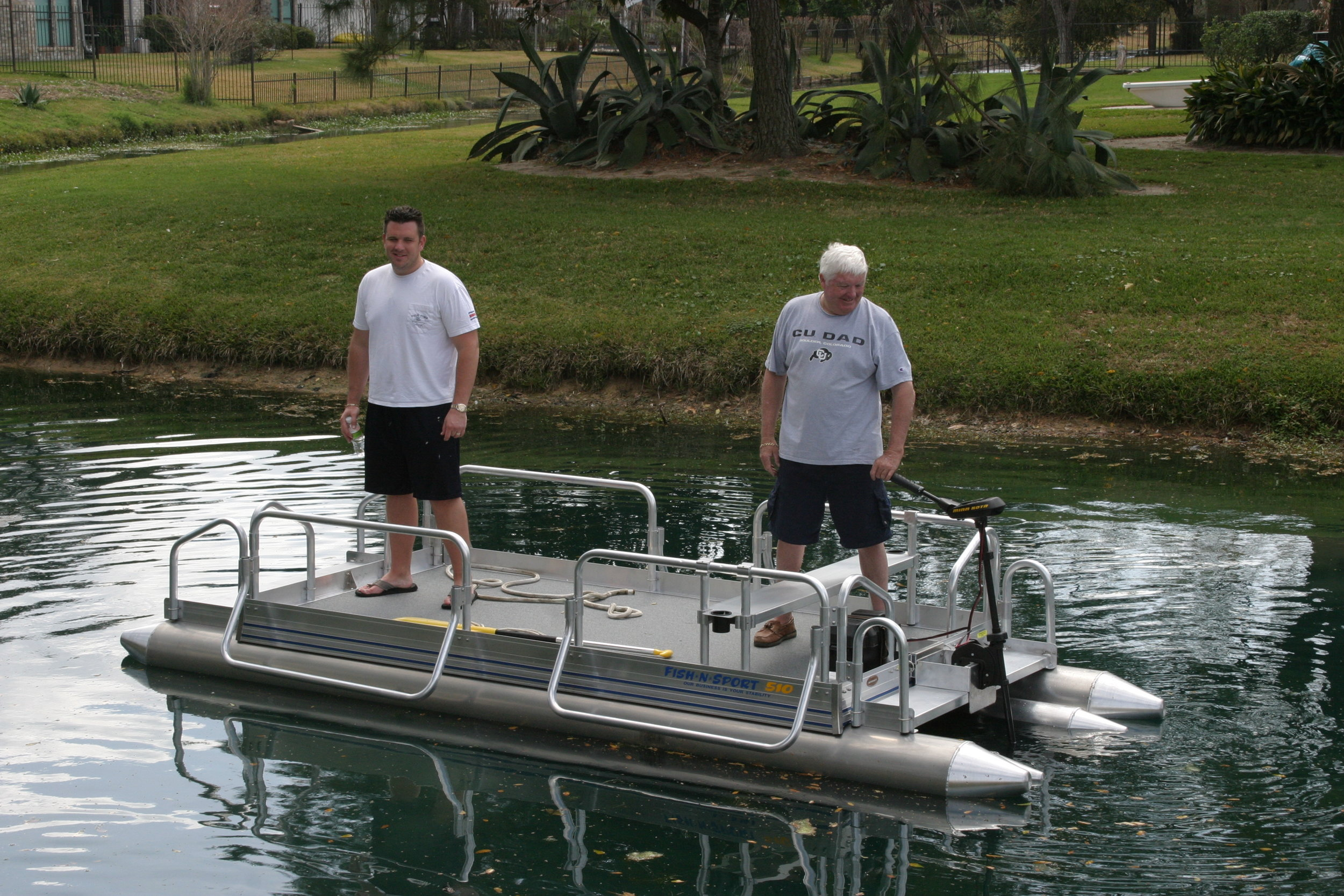 Father with Son showing how stable the Fish N Sport is on the water. Notice the floats are only drafting about 3 inches with these two big men on board. Our boats are designed to sit on the water more than in it.
