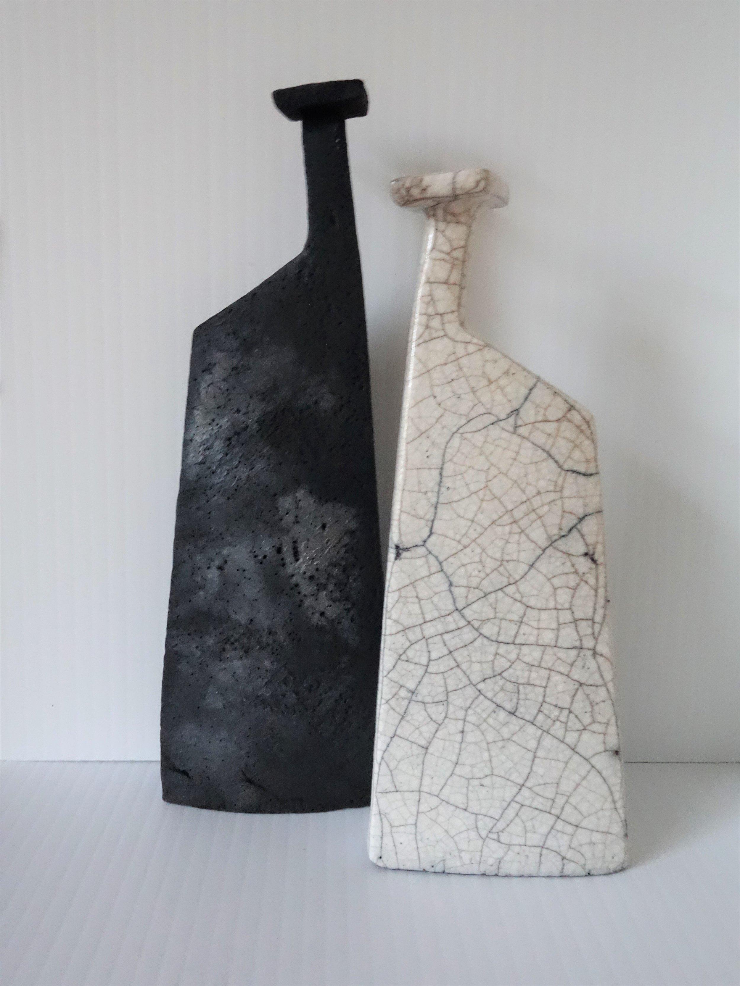 (LEFT)  Title: Matt Black Bottle (square top) Size: 19 cm (h) x 7 cm (w) Medium: Smoke Fired Price: £90  (RIGHT) Title: White Raku Bottle (square top) Size: 17 cm (h) x 7 cm (w) Medium: Raku  Price: £90