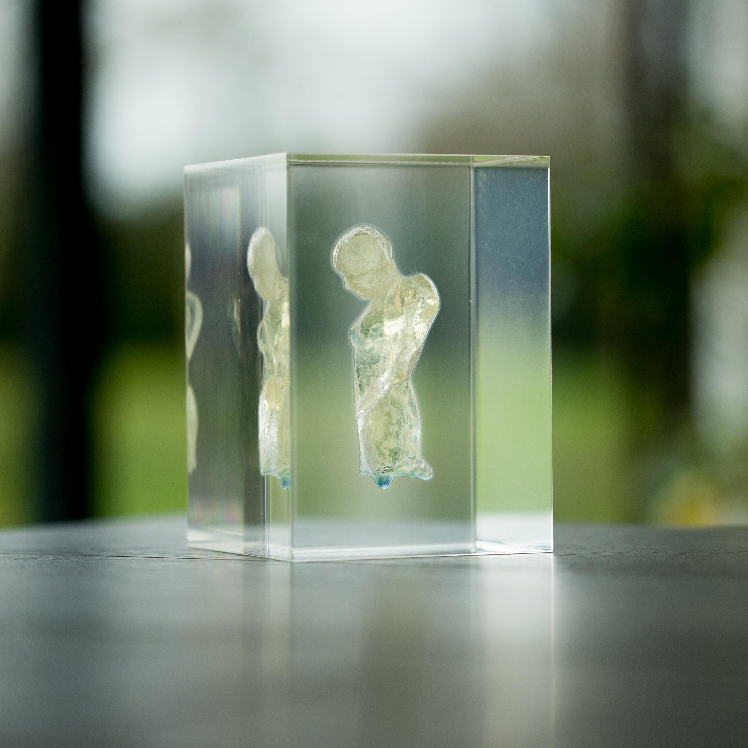 Artist: Kate Viner  Title: Encapsulation - Fallen Angels Series  Size: 14.5 x 10 x 10 cm  Medium: Glass figure in a perspex cube  SOLD