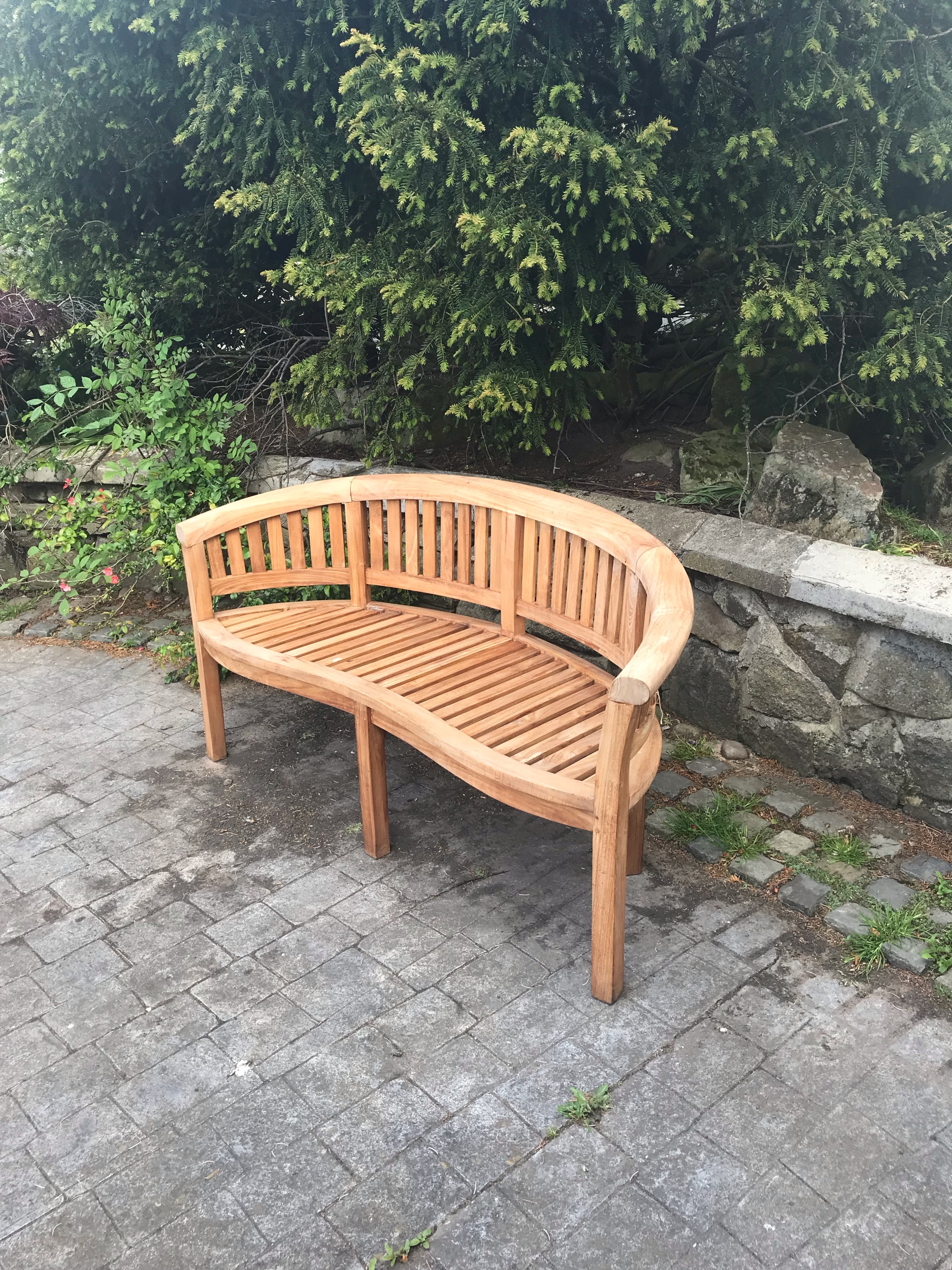 A solid teak bowed complete garden seat. £250. Free delivery locally