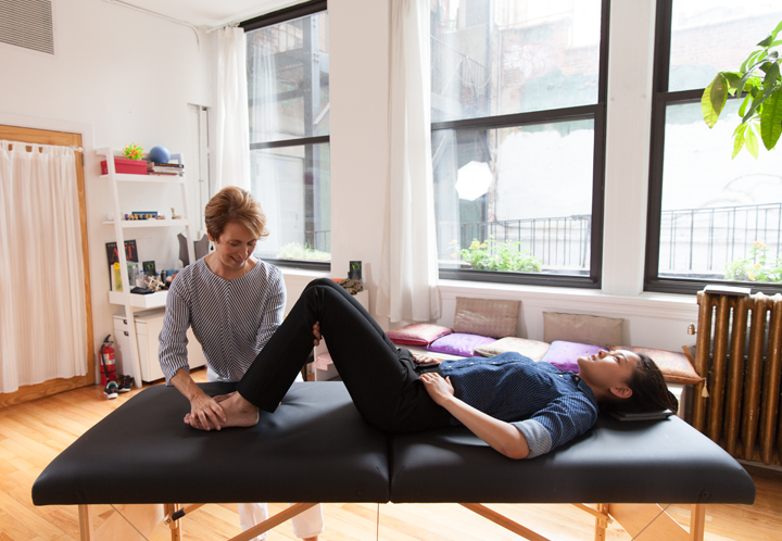 Belinda takes a client through some Alexander Technique table work exercises for tension relief. The client lies down on a table while Belinda guides the clients limbs to release.