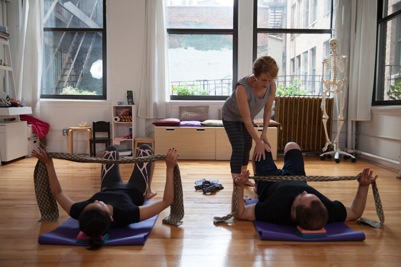 Belinda teaches Alexander Technique to two actors lying on the ground on top of yoga mats with small foam support blocks beneath their heads. They move fabric bands through the air playing with supportive resistance.