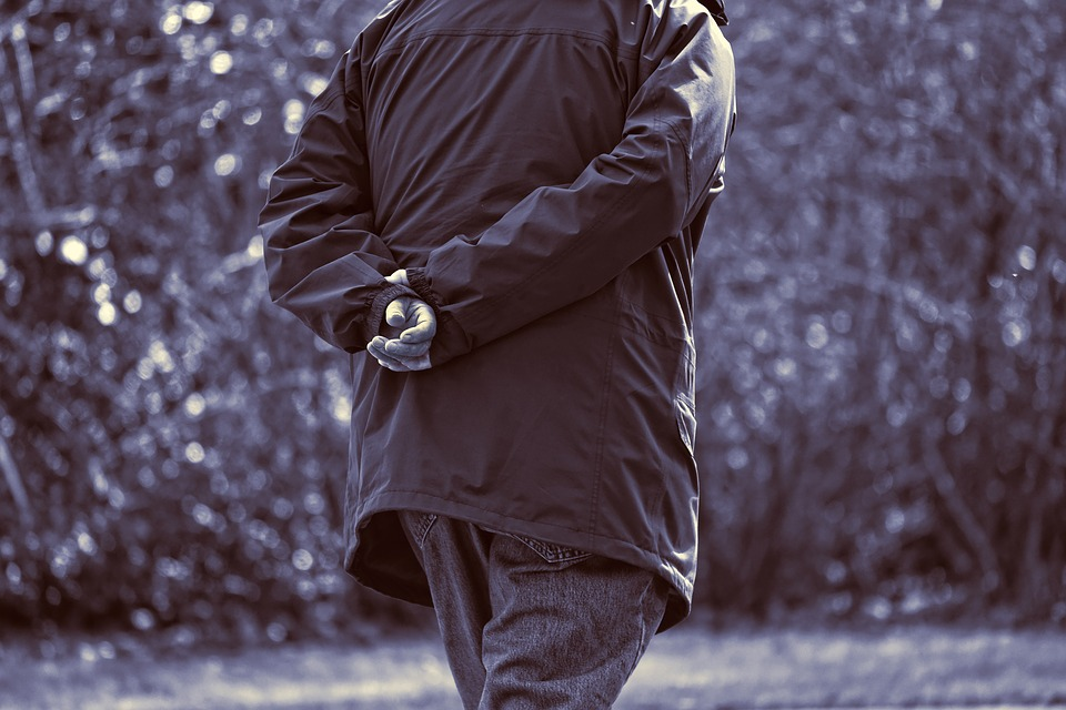 The back side of a man walking away in a light jacket and jeans. His arms are crossed behind his back as he walks. What does this say in reference to Lecoq gesture?