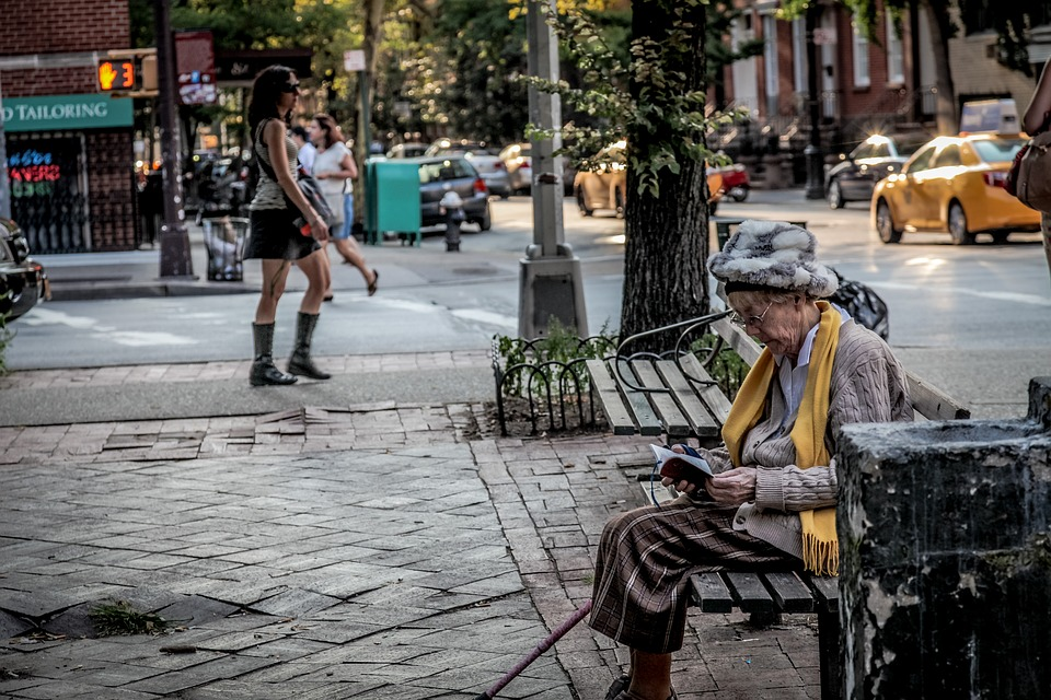 A street in New York City. An old woman sits on a bench reading, some young women walk. It is a warm summers day. Start walking down the street and practice this Alexander Technique a, Acting, and Presence Exercise.