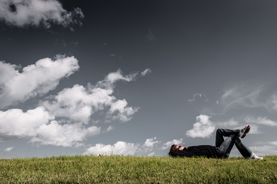 A person relaxing in the grass on a fall day. When you're lying down, you can feel supported by the earth. You can feel gravity moving through you towards the center of the earth, and an equal and opposite pull in reverse helping you stay buoyant and reaching up. You are supported.