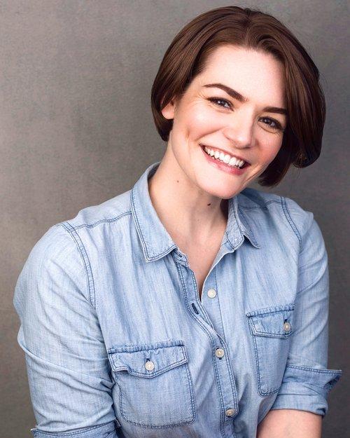 Headshot of NYC Actress: Caitlin Diana Doyle. Caitlin smiles at the camera in a light denim shirt.