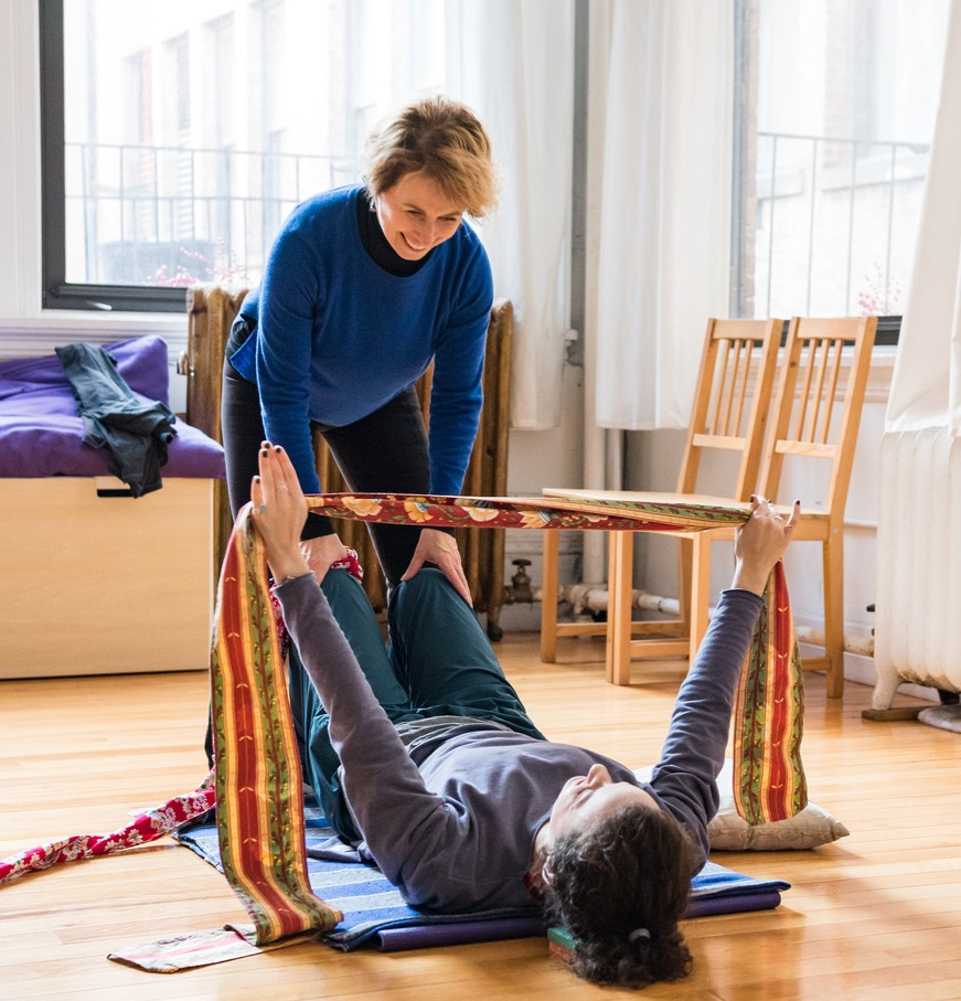 Belinda guides an actor laying down on the ground through an exercise where the actor practices only using the necessary amount of effort to push a strap of cloth into the air. This shows the actor where they are holding unnecessary tension and gripping.