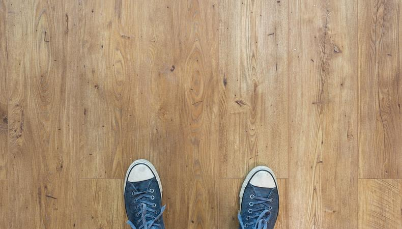 Two blue converse sneakers on the floor from the point of view form a person looking down at their feet.