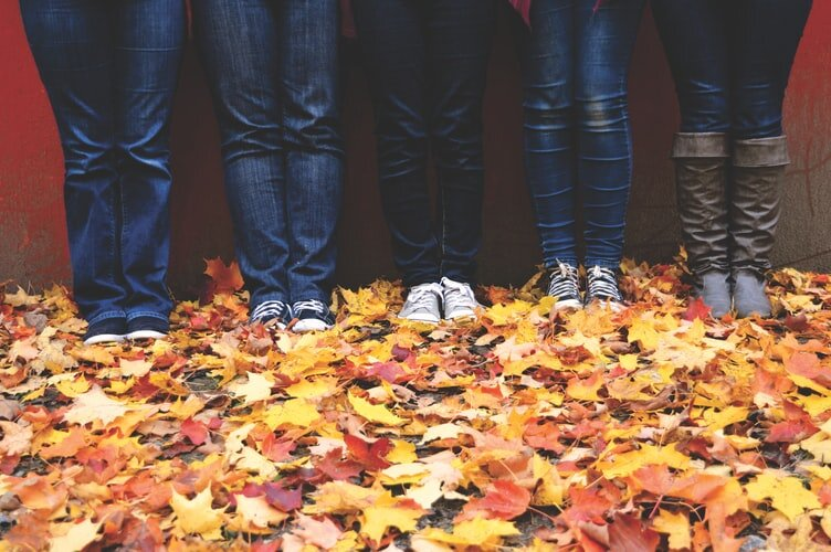4 young people stand against a wall in jeans and sneakers. It's fall and there's leaves on the ground. They're doing an Alexander Technique etude where they see if they can do less while sliding down the wall.