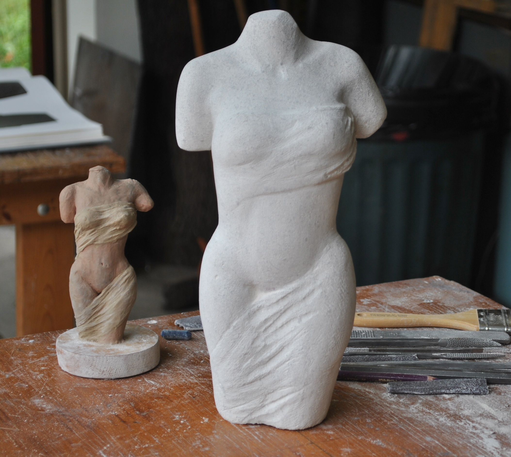 Her stone carving is nearing completion. Her clay model (maquette) is more clearly visible here.