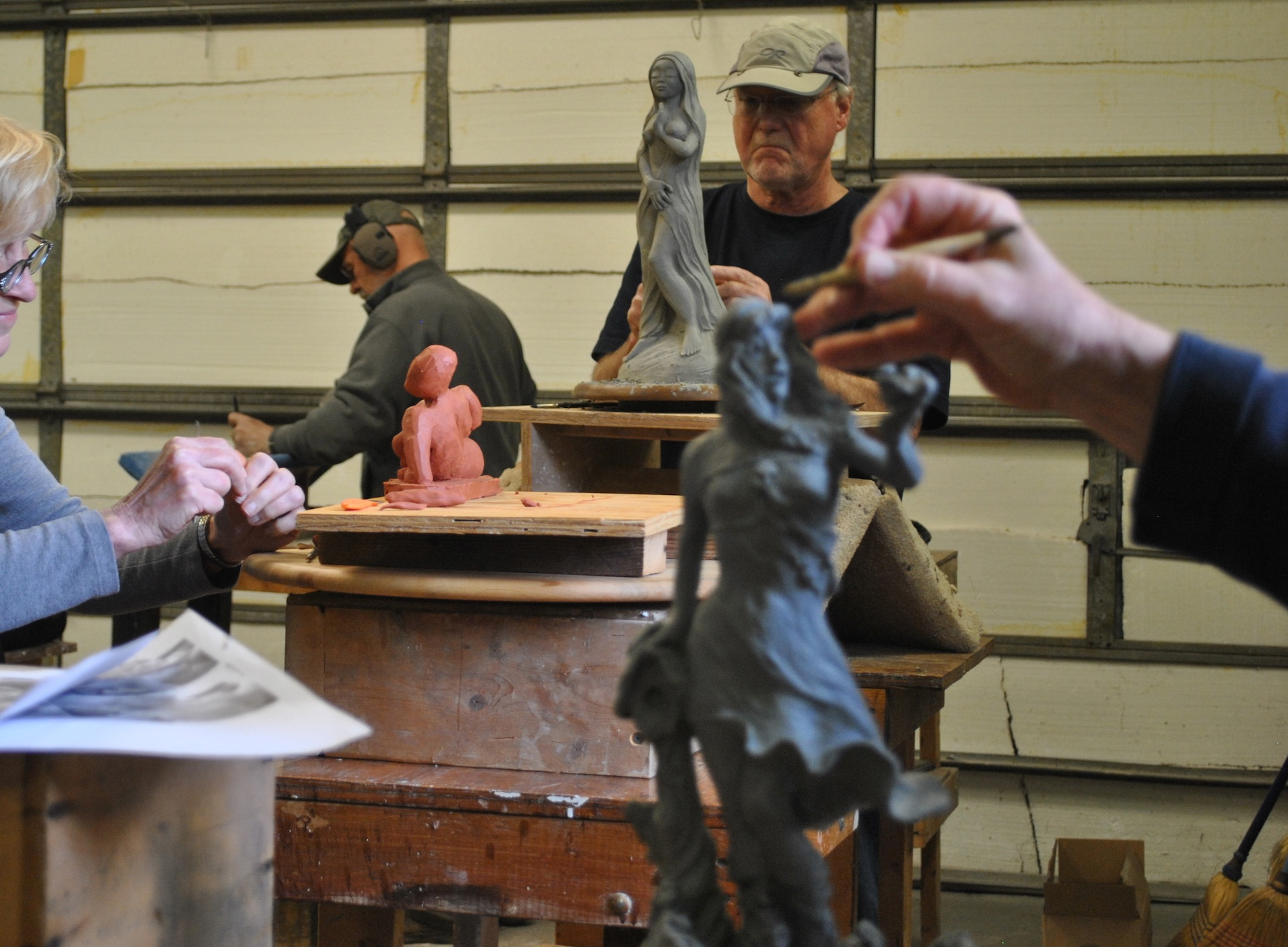 Several more experienced sculptors' clay sculptures underway.