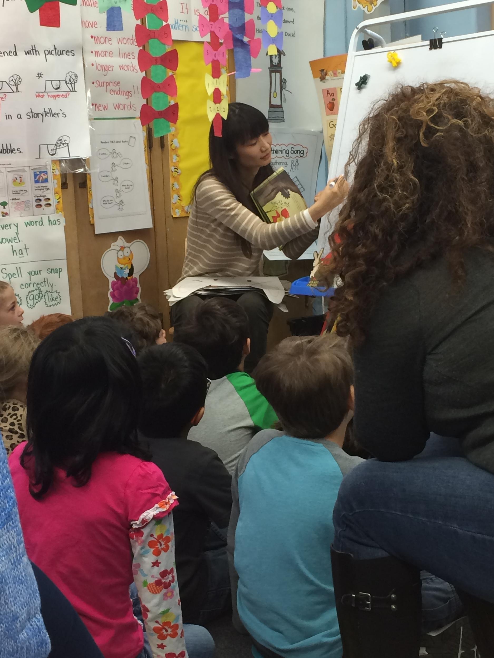 Naoko Stoop demonstrates her illustration technique to a class of kindergarten students.