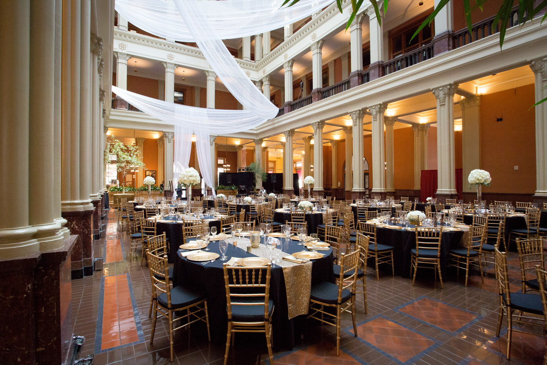 19-the-landmark-center-st-paul-mn-wedding-photographer-reception-table-settings-black-gold-charger-plates-linen-effects-drapery-mahonen-photography.jpg