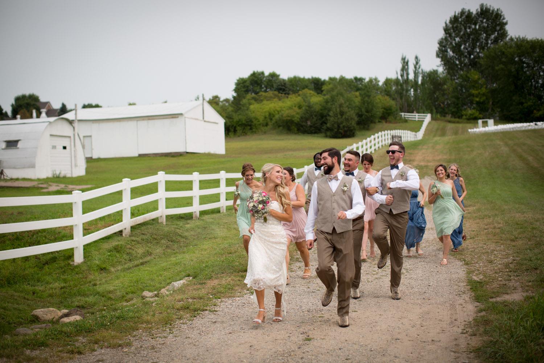 04-dellwood-barn-minnesota-wedding-photographer-farm-dirt-road-fun-bridal-party-photos-running-skipping-mahonen-photography.jpg