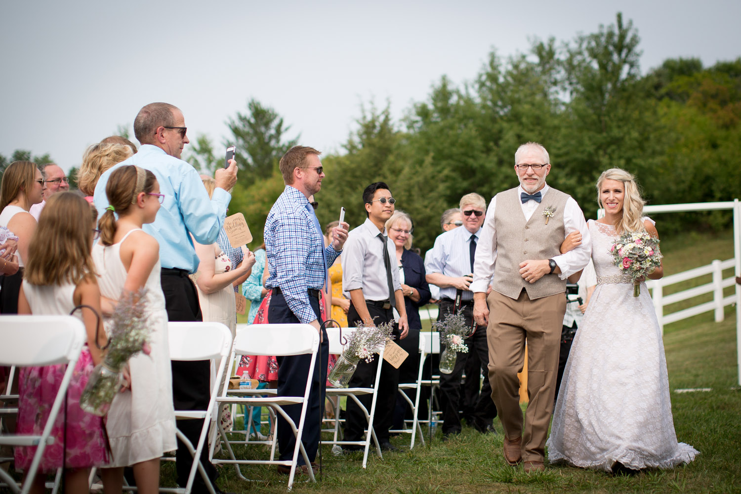 15-dellwood-barn-weddings-minnesota-wedding-photographer-outdoor-summer-ceremony-grassy-field-here-comes-the-bride-father-daughter-mahonen-photography.jpg