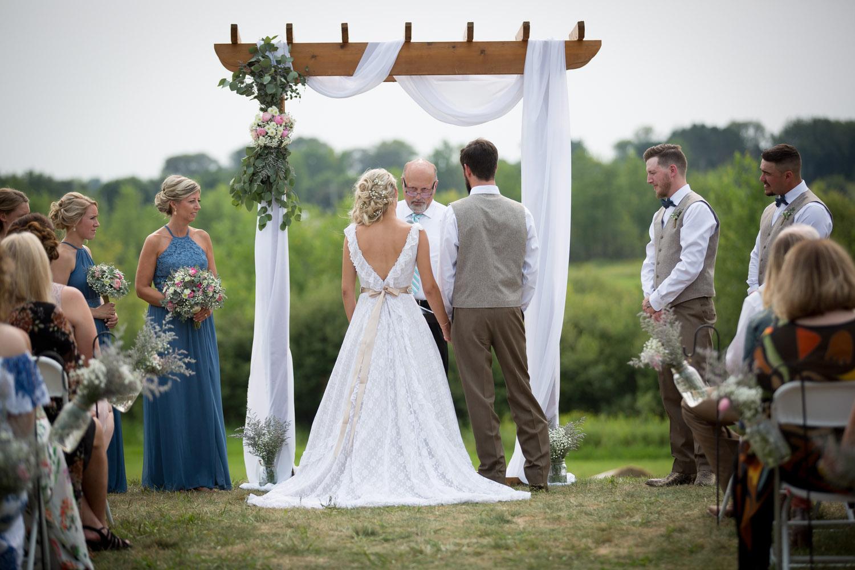 18-dellwood-barn-weddings-minnesota-wedding-photographer-outdoor-summer-ceremony-grassy-field-wooden-craftsman-style-arbor-mahonen-photography.jpg
