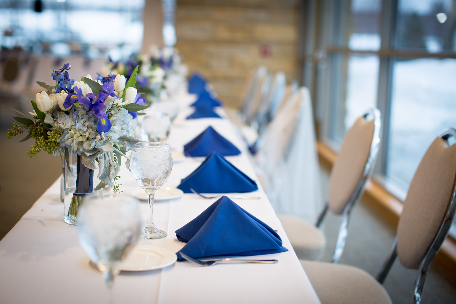 20-eagan-community-center-weddings-minnesota-winter-rain-wedding-reception-head-table-blue-napkins-mahonen-photography.jpg