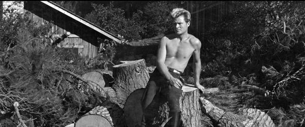 Brett Weston sitting on wood pile