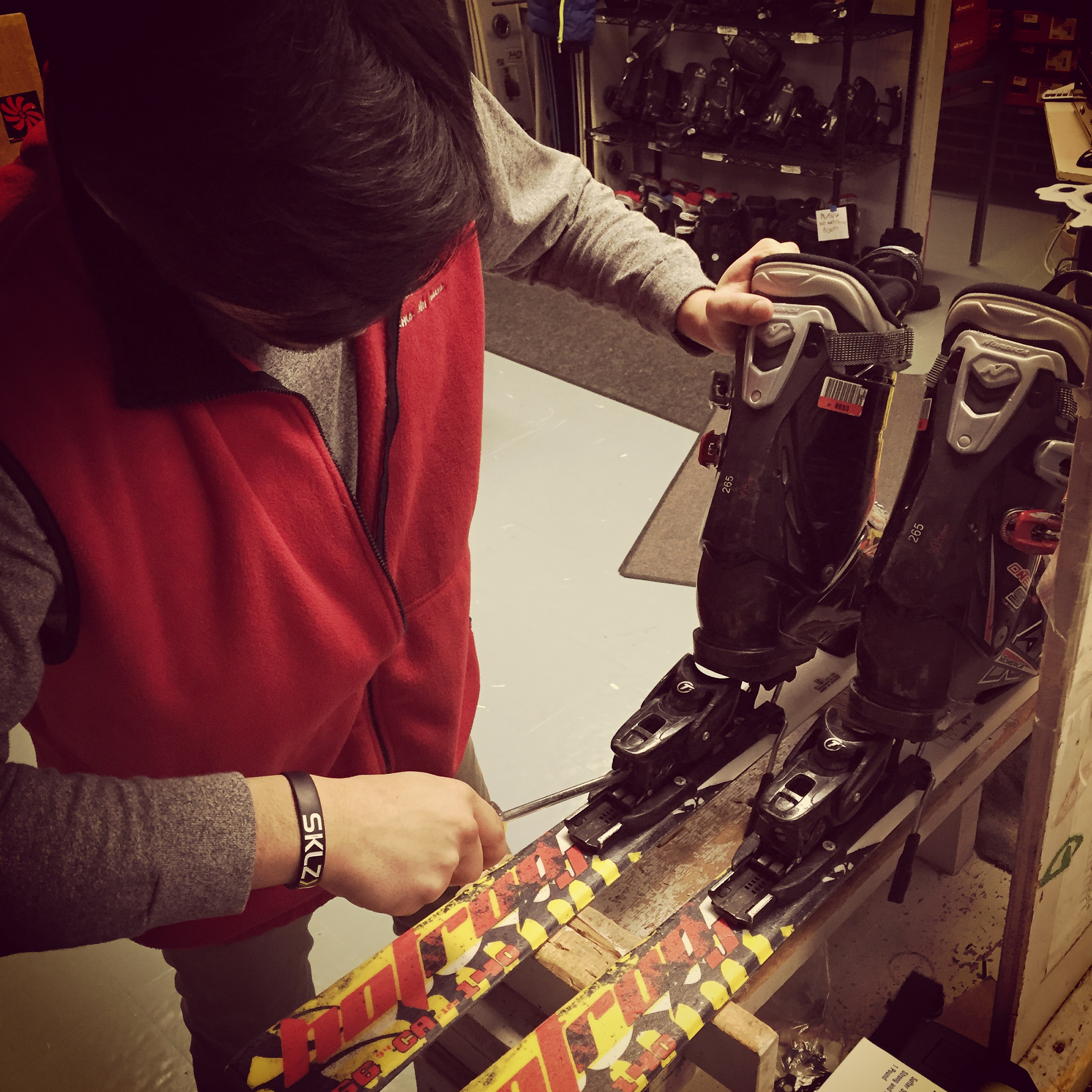 Williams ski service team member setting up bindings on rental skis