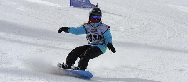 Female snowboarder making carving turns through gates.