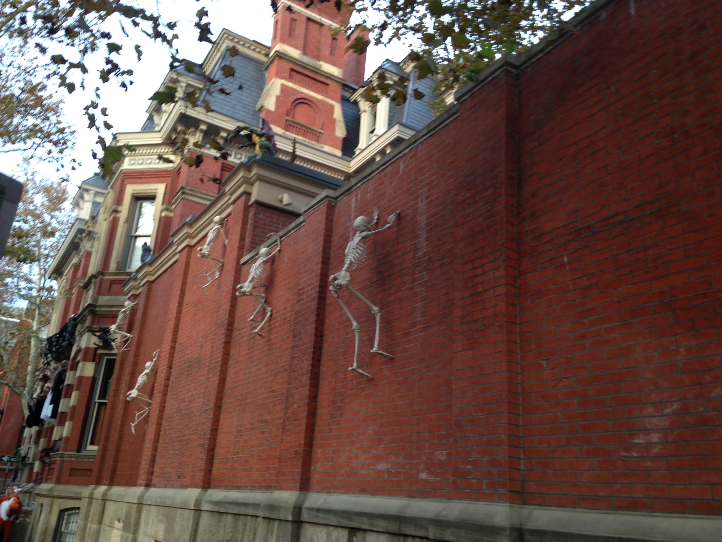 Skeletons scale the wall of this mansion