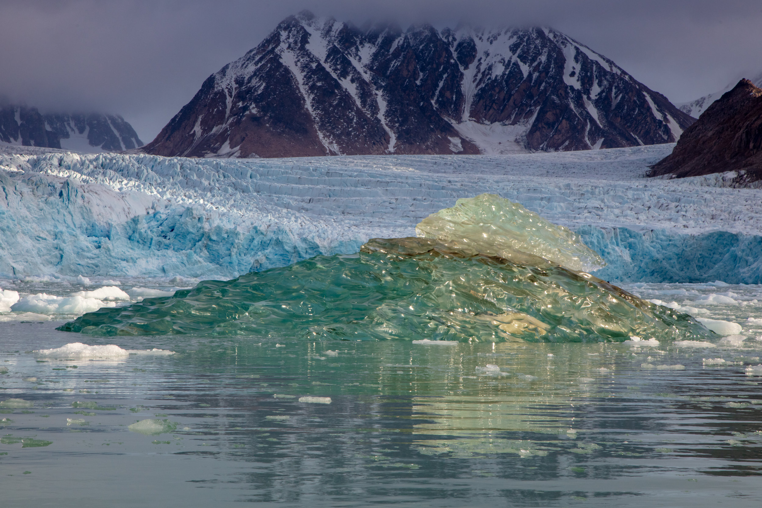 A blue iceberg drifts out to sea along the mars-like tundra of Northern Spitsbergen. Today, the archipelago of Svalbard is located just a few hundred miles from the North Pole, but this was not always the case. When these brilliant red sandstones formed 400 million years ago, the original land mass that would become Svalbard was nearly at the equator, 6000 miles south. Newly formed mountains were eroded by rivers that flowed through the once hot desert climate and the sand and mud deposited, compressing and forming stone. Though Svalbard has seen many changes along its slow journey northward, the modern geological changes are now driven by humans rather than the natural forces of nature. As the climate warms, the rapid disappearance of ice is exposing the barren rocks of Svalbard once again, possibly for the first time in thousands of years.