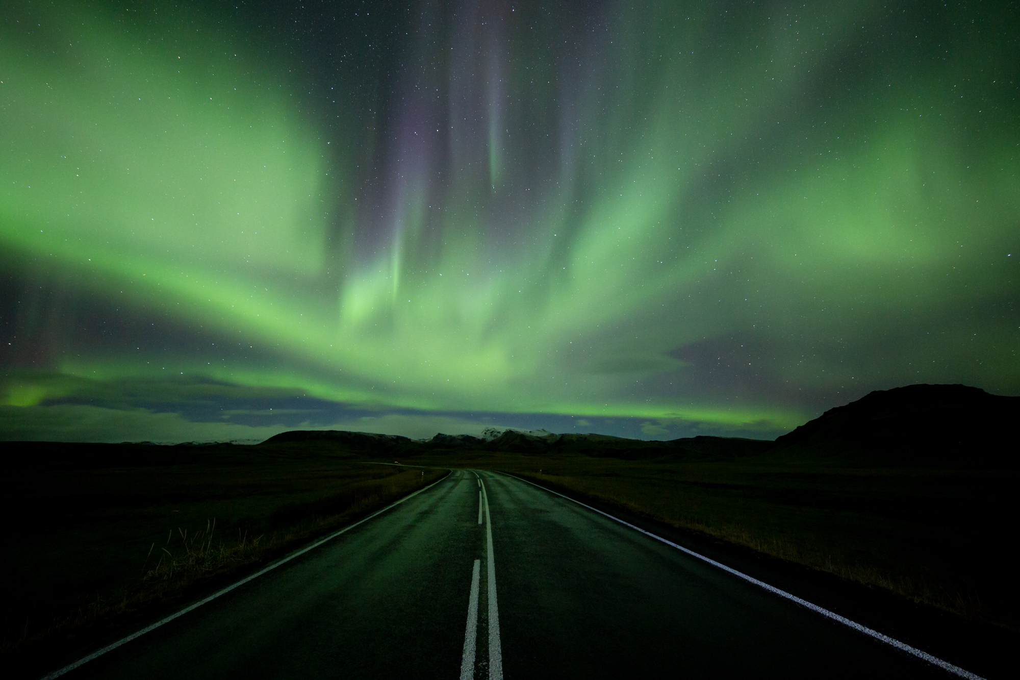 """The Road North""  The Aurora Borealis dances in the sky during a solar storm in early October. Though I have spent a lot of time in the far north, I had never had the chance to see the colorful lights that illuminate the poles of the planet when the sun dips far enough below the horizon to create a dark sky. The flickering and dancing curtains of the aurora are a humbling sight because without them, life as we know it would not be possible. The earth's inner core and unusual atmosphere block the sun's powerful radioactive storms, allowing life as we know it to flourish oblivious to the ferocity of outer space."