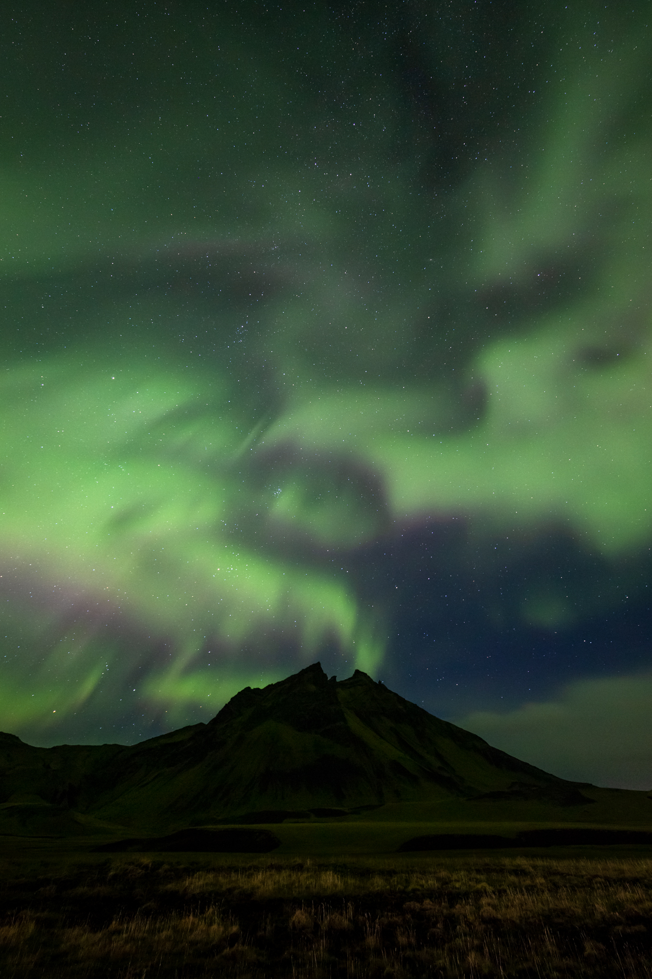 A swirling river of light and dark created by the Aurora Borealis dances atop a pyramid shaped mountain in the South of Iceland during a solar storm.  Vibrant and dancing auroras occur when either a sun spot, flare, or coronal hole on the sun create a cosmic stream of energized particles known as the solar wind, that blows at nearly one million miles per hour towards our remarkably resilient planet. During such a storm, these energized particles are deflected by earth's magnetic field and are funneled near the poles where their energy is emitted as the brilliant Northern Lights.