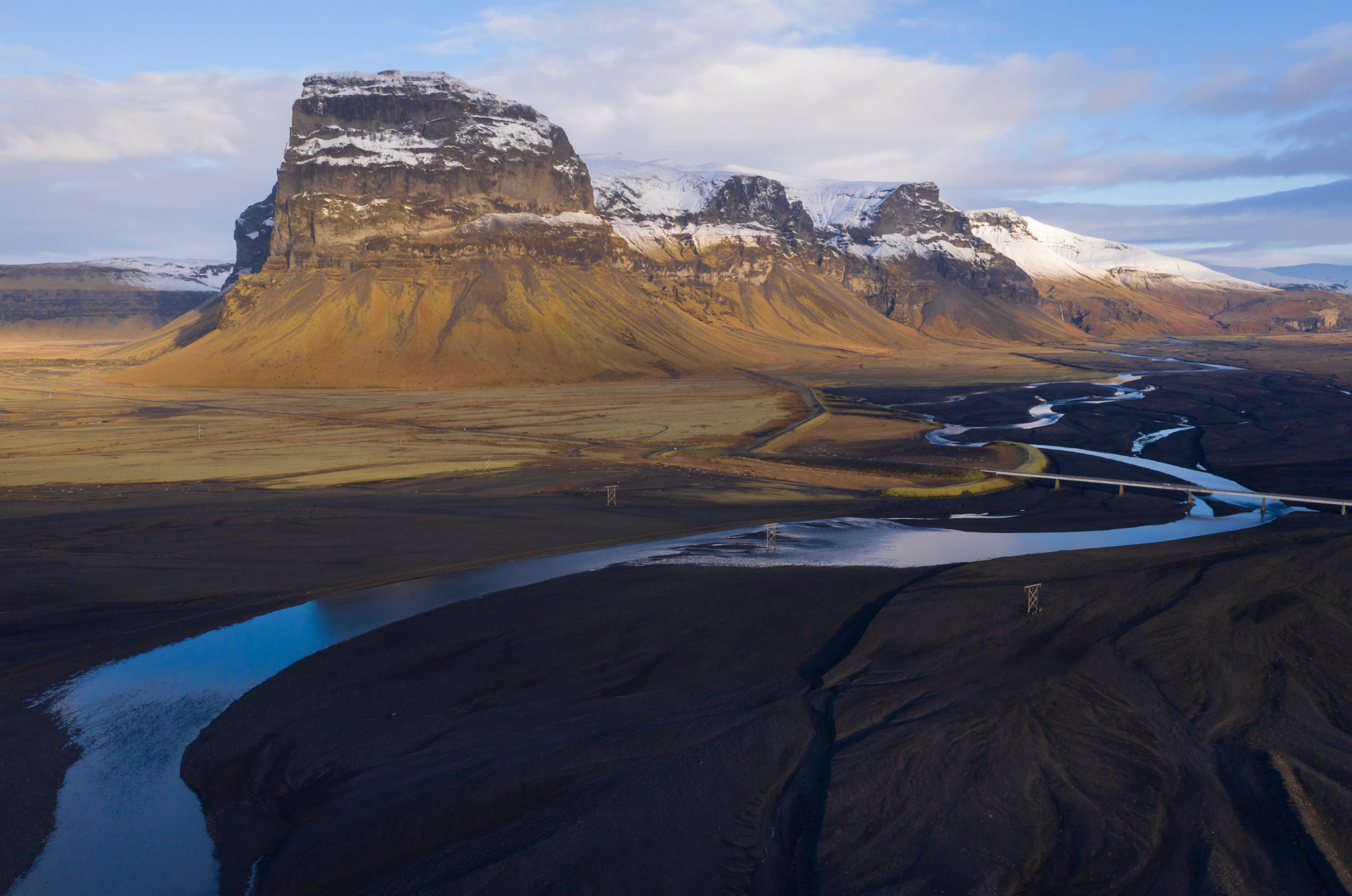 A mellow glacial stream glows blue and white from the reflected sky as it creates elegant s-curves along the dramatic bounding edge of the Skeiðarársandur