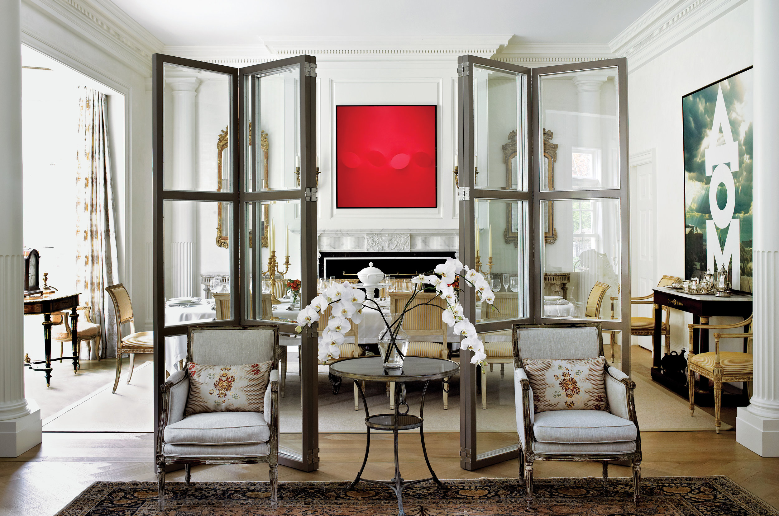 large bifold glass screens separate the living and dining room in this georgian estate. contemporary art contrasts with traditional antiques.
