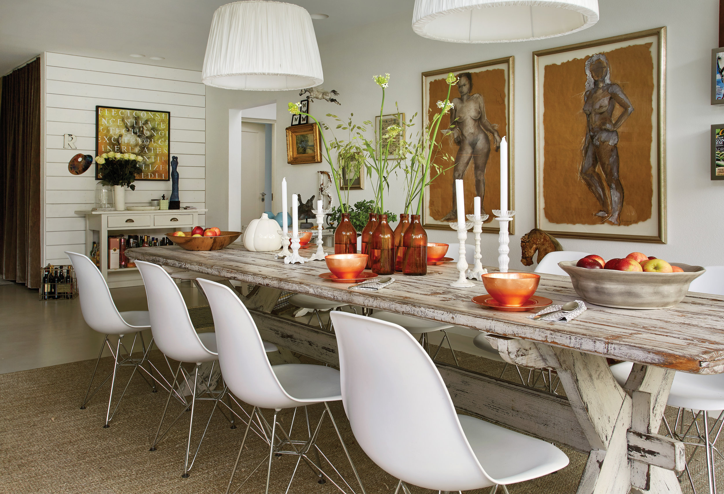 dining room from a project in sweden mixes mid-century eames chairs with vintage farmhouse table.