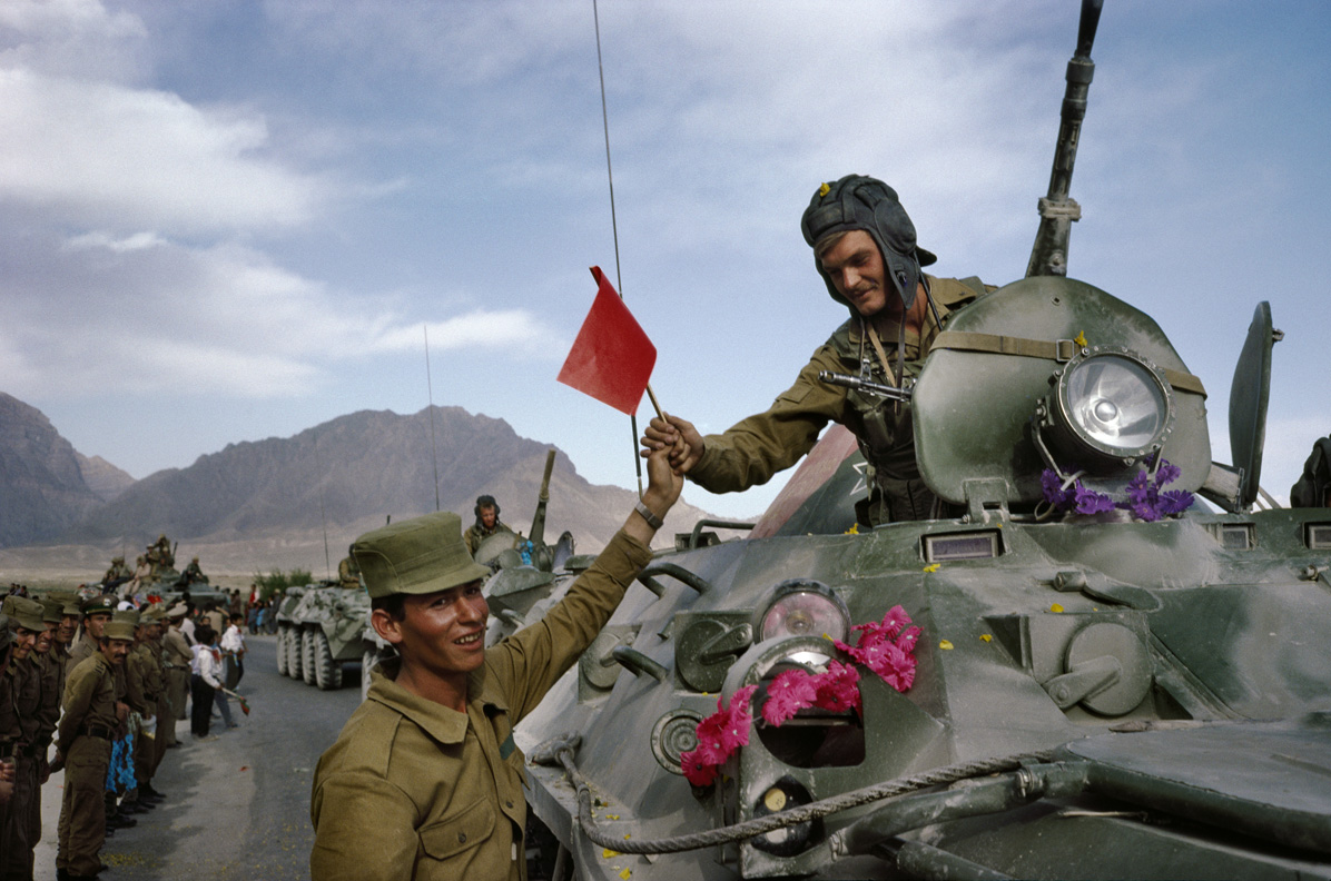 Afghan soldier hands red solidarity flag to Soviet officer, 2010