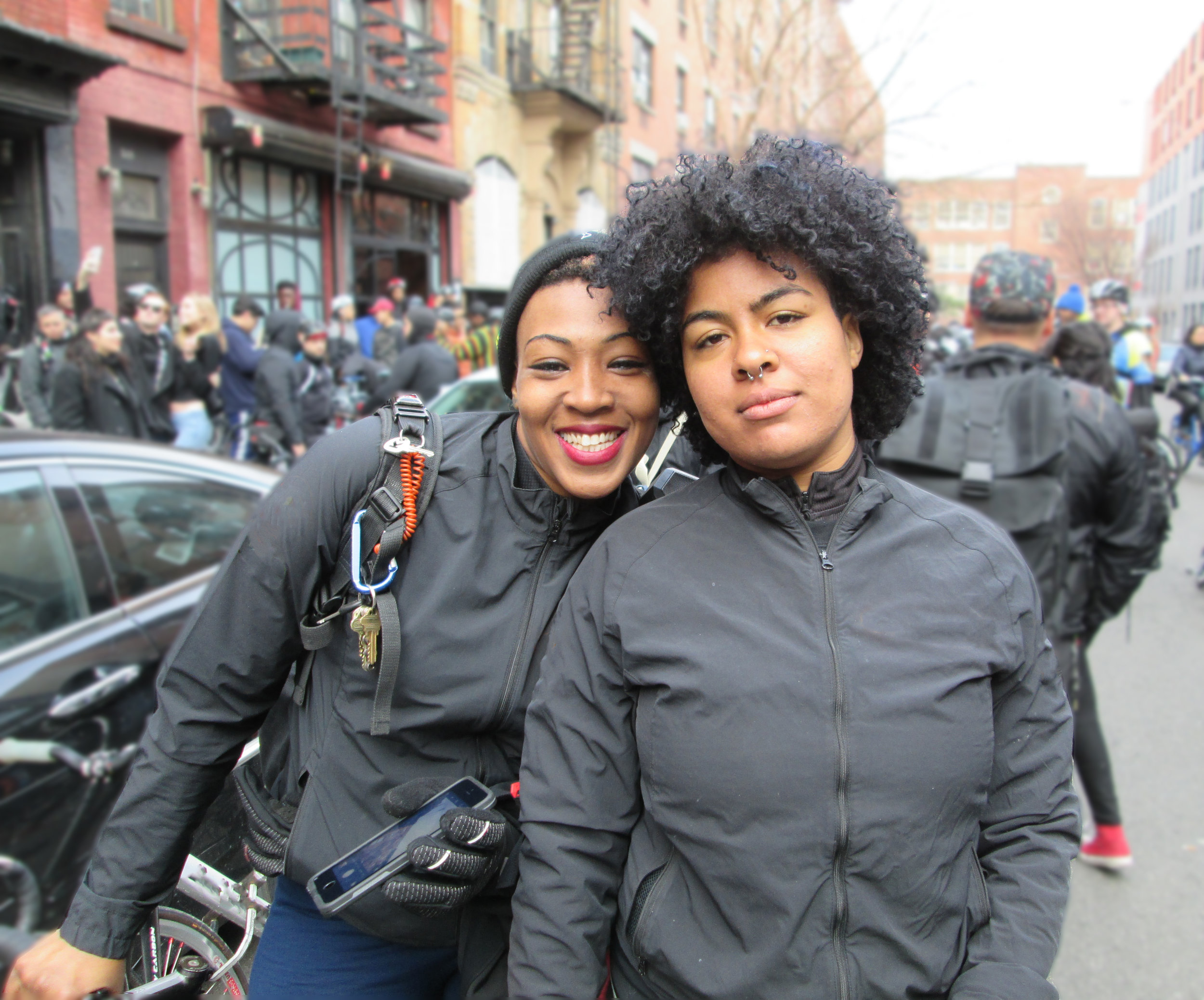 Two young African American women urban cyclists and bicycle messengers at Monster Track, an annual NYC bicycle messenger street race. Alphabet City, 2015