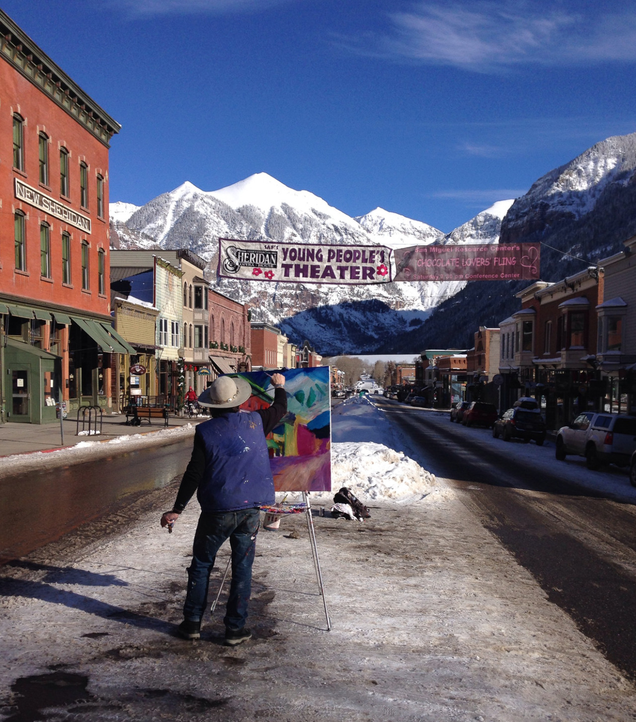 An artist paints in the middle of the street in Telluride, Colorado
