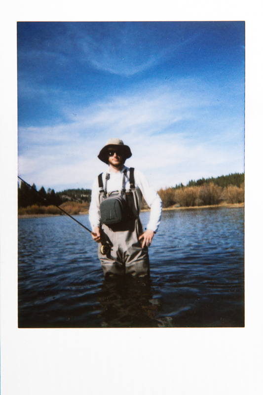 Polaroid of Jeff in his waders in the Truckee River while dry flyfishing